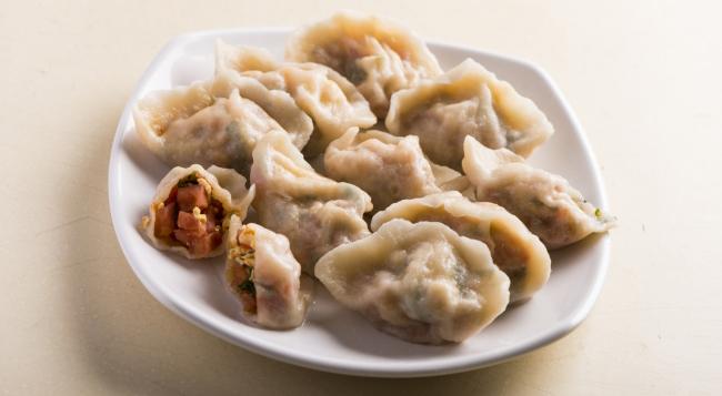 """这种食物,在世界多国的饮食文化中皆占一席之地,近至日韩,远至波兰,遍地开花。烹调方法变化万千,或蒸或煎或炸或焗或水煮尽皆宜;连名字也大不相同:匾食、子孙饽饽、 gyoza、mandu、mant、gomboc、 pierogi、samosa…… 在华人世界,我们称呼这种食物为""""饺子""""。 中国饺子源自北方新年传统。北方人取其""""更岁交子""""之意头,视之为新年的重要应节食品。除夕夜大家包好饺子,半夜十二时就会开始夹起一双""""形如月"""
